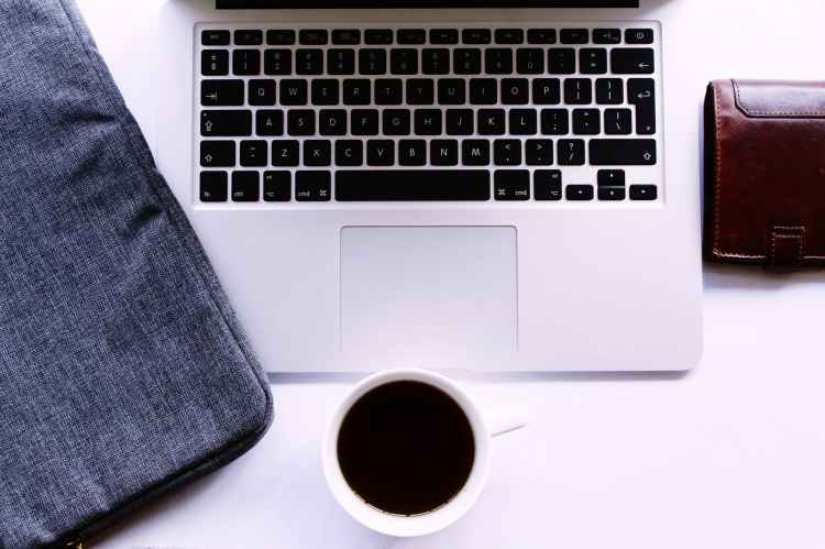 photo of coffee of cup near laptop and wallet
